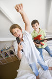 Two Boys Standing On A Bed Playing. Two Boys Standing On A Bed, Playing Guitar And Singing Into A Hairbrush Royalty Free Stock Images