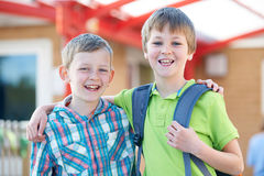 Two Boys Standing Outside School With Book Bags Royalty Free Stock Photos