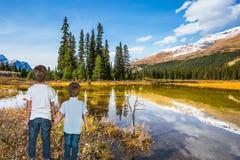 Two boys standing on shallow lake Stock Image