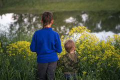 Two boys are standing by the water. Royalty Free Stock Image