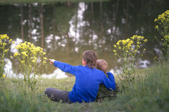 Two boys are standing by the water. Stock Images