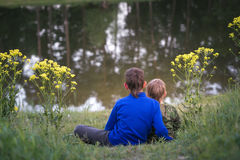 Two boys are standing by the water. Royalty Free Stock Photo