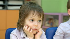Two boys staring at something. Five year old children in a classroom stock video footage