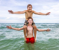 Two boys strike a pose in the ocean Royalty Free Stock Image
