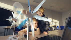 Two boys studying small models of a wind turbine. stock video footage
