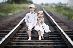 Two boys with suitcase on railways Stock Image
