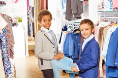 Two boys in suits hold clothing item at the shop Royalty Free Stock Photography