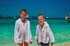 Two boys on sunny tropical beach look at camera. Children are dressed in shirts to protect themselves from ultraviolet exposure. Two boys on sunny tropical Royalty Free Stock Photos