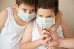 Two boys in surgical mask looking at the hand with syringe Stock Photography