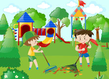 Two boys sweeping leaves in park Stock Photo