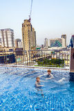 Two boys swim in a rooftop pool Stock Photography