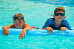 Two boys in the swimming pool 1. Two happy boys in the swimming pool. Blue water. Brothers Royalty Free Stock Image