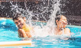 Two boys at the swimming pool splashing water and having fun. Friends playing on the water of a summer day Royalty Free Stock Image