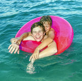 Two boys in a swimming tube have fun in the ocean Stock Photos