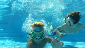 Two Boys Swimming Underwater Together Royalty Free Stock Photos