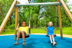 Two boys swing together and hold chains of swings. Two smiling happy boys swinging together and hold chains of swings Royalty Free Stock Image