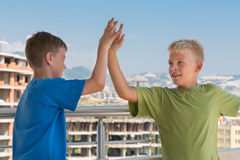 Two boys in T-shirts are greet each other. Two smiling boys in colored T-shirts are greet each other on the background of building under construction stock images