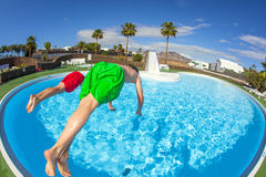 Two boys take a header into the pool. In tropical landscape Stock Images
