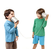 Two boys talking on a tin can phone. Isolated on white Royalty Free Stock Photo