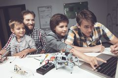 Two boys a teenager and an adult male are sitting in the workshop and constructing a robot. Two boys, a teenager and an adult male, sit in the workshop and Royalty Free Stock Photography