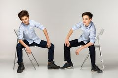 Two boys teenagers in blue shirts and black pants stock photo