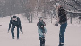 Two boys and there parents playing snowballs. 4K stock video footage