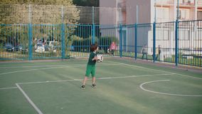 Two boys throw a ball in a basketball basket. Two boys throw the ball into a basketball basket on the playground at school. One is dressed in pants and a T-shirt stock video footage