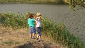 Two boys throw stones into the lake in summer day. Two small active boys throw stones into the lake in the hot summer day. Two children play on the shore of the stock video