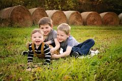 Three boys on a farm. Two older brothers tickle baby brother hay bales in background Stock Photos