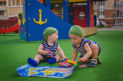 Two boys toddlers pirate costumes (sailors) playing on Playgroun Stock Image