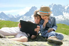 Two boys with tablet PC in mountains Stock Photos