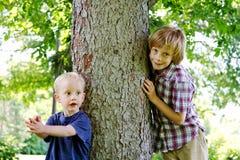 Two boys beside tree. Two boys poising beside tree in park Stock Image