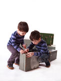 Two boys trying to open wooden box on a white background Royalty Free Stock Images