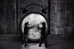 Two boys, trying to pull clocks hand backwards, creative concept Royalty Free Stock Images