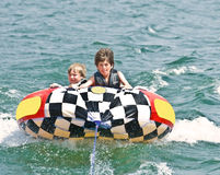 Two Boys on Tube Behind Boat. Two brave young boys on a tube being pulled behind a boat. Very serious expressions on their faces. 9 and 10 years old stock image