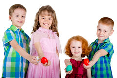 Two boys and two girls hold Easter eggs in straight arms Stock Images