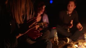 Two boys and two girls sitting by the fire at night and singing songs. Happy friends singing songs and playing guitar stock video footage