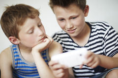 Two boys using a cellphone, smiling Royalty Free Stock Images