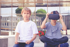 Two boys with virtual reality goggles and tablet computer Stock Image