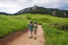 Two boys walk mountain path Stock Images