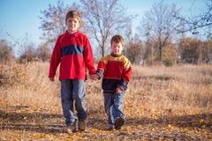 Two boys walking on autumn park Stock Photo