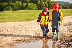 Two boys walking through a mud puddle Royalty Free Stock Photography