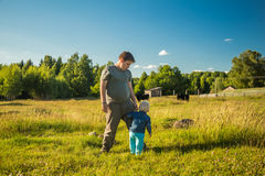 Two boys watching cows in a meadow. Stock Photo