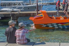 Two boys on the waterfront, Queenstown, New Zealand. Back view. With selective focus royalty free stock images