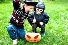 Two boys wearing halloween costumes. Attacking pumpkin Royalty Free Stock Photo