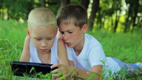 Two boys in white clothes lay on the grass in the. Park and play on the tablet computer games, chatting with friends on the social  networks stock footage