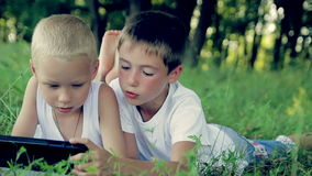 Two boys in white clothes lay on the grass in the stock video footage