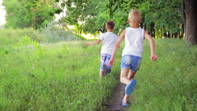 Two boys in white clothes running in the park stock video footage