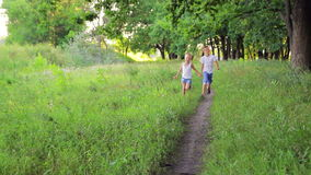 Two boys in white clothes running in a park stock video footage
