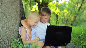 Two boys in white clothes sitting in a park on the stock footage